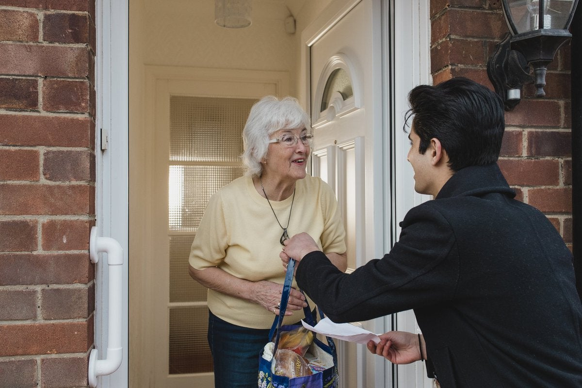 young man delivering groceries to senior woman.