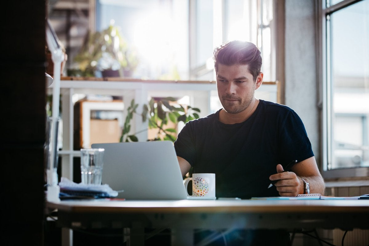 young man sitting at desk using laptop and thinking