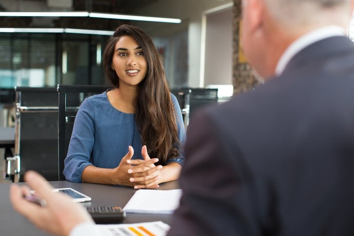 A young woman sitting across the table from a man in an office for a job interview.