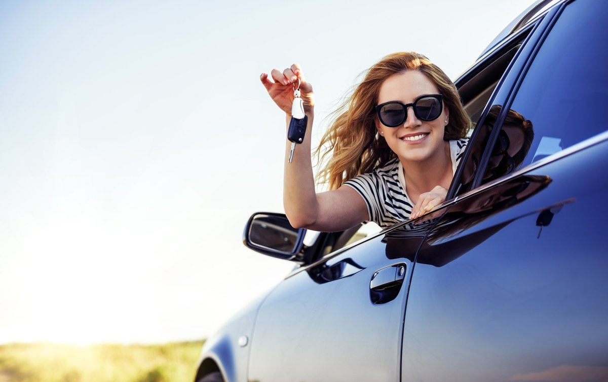 young woman leaning out of car window and holding keys -- new car purchase