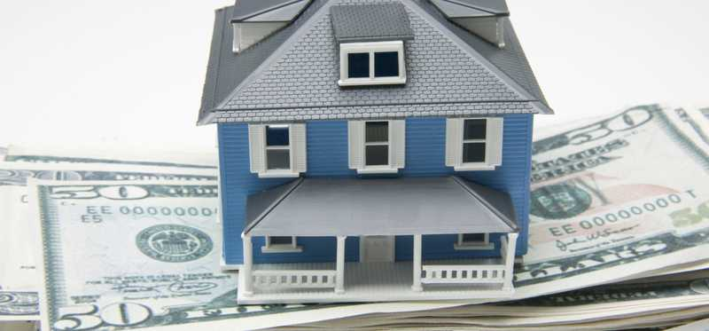 A blue model home sitting on stacks of cash.