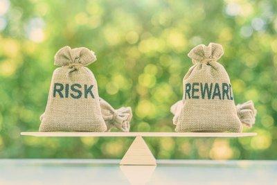 Balanced burlap bags saying Risk Reward
