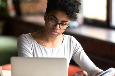 Woman in glasses is looking at laptop.