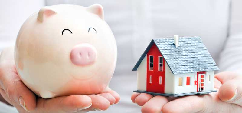 Hands holding piggy bank in one hand and model home in the other.