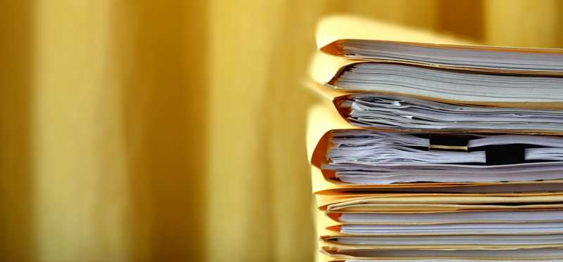 A stack of manila folders full of documents.