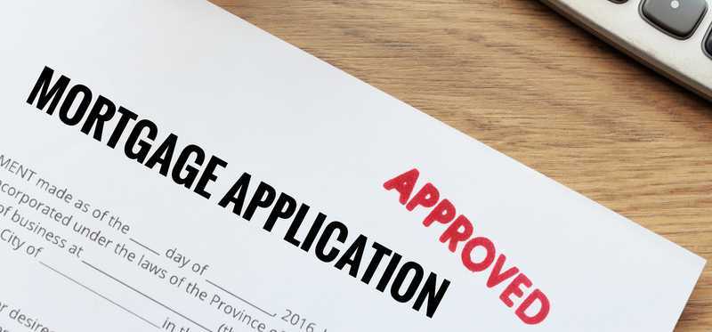 A mortgage application stamped with red approval stamp.