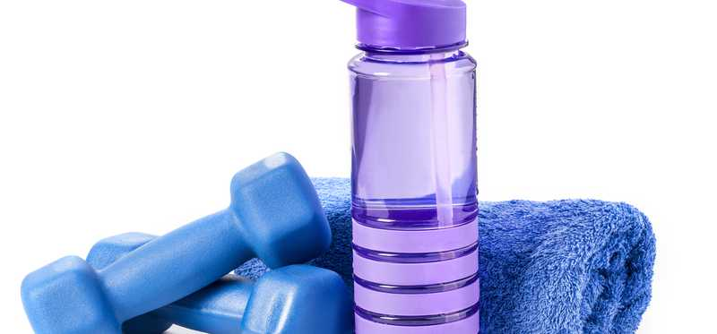 A reusable plastic water bottle next to dumbbells and a towel.