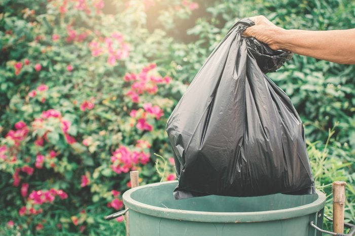 A garbage bag being thrown in the trash can with red flowers in the background