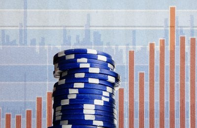 Blue poker chips with investment related imagery in the background