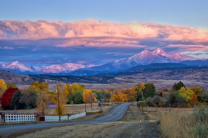 A colorado countryside at sunset with mountains in background.