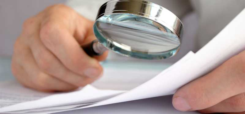 A magnifying glass being held over some paperwork.