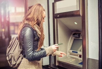 Woman removing funds from an ATM.
