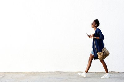 Woman walking with smartphone and earbuds