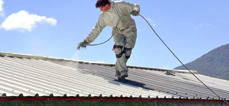 Man spraying a white roof.