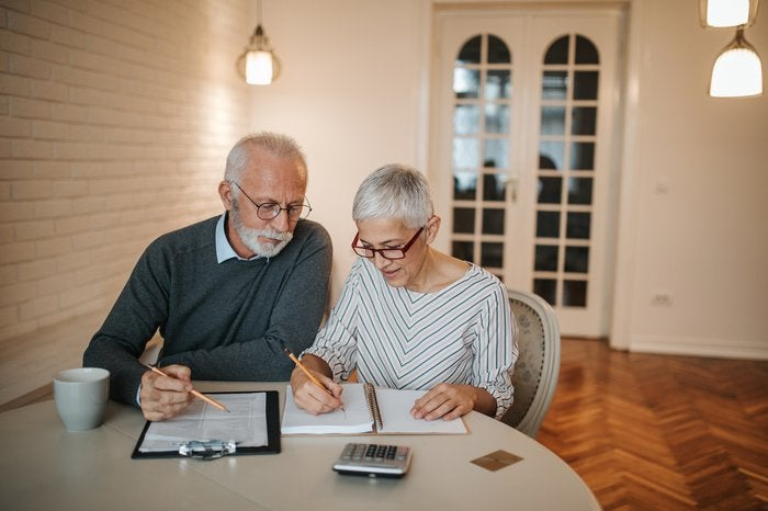 Older couple writing in notebooks together.