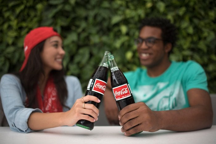 A young adult male and female enjoying bottles of Coke together.