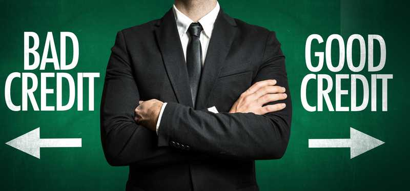 Man in suit standing between arrows point in the directions of good credit and bad credit.