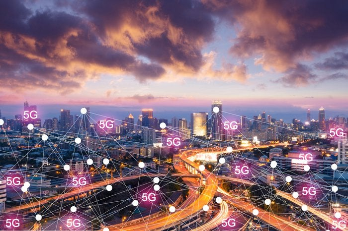 View overlooking a large city that is lit up with a network of 5G ping points