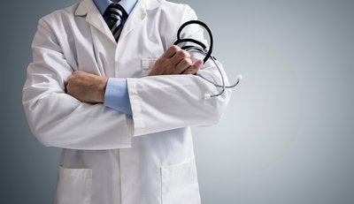 A doctor standing in his white coat with arms crossed.