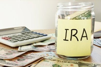 Jar of money labeled IRA sitting next to calculator.