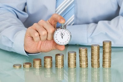 A businessman holding a stopwatch behind an ascending stack of coins