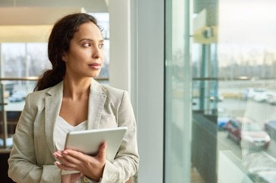 A businesswoman holding a tablet while looking out a window.