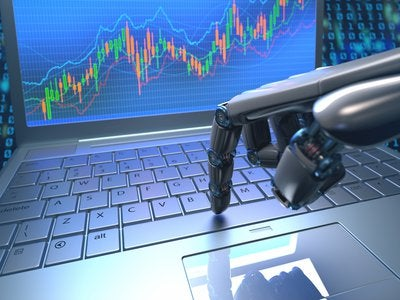 A robot's hand pressing a key on laptop that has rising stock charts on its screen.