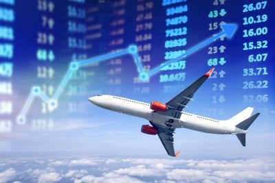 Airplane flying with stock market numbers and a chart in background.