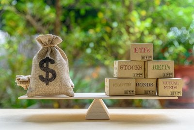 Burlap sack of money balanced on a seesaw versus stocks, bonds, and more