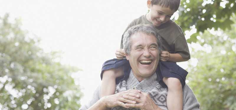 Older man with grandson on his shoulders.