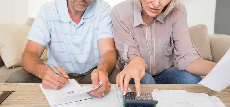 Mature couple using calculator with paperwork.