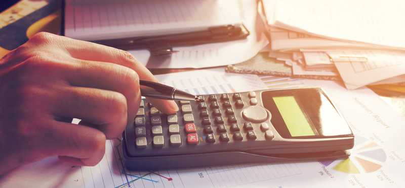 A hand using a calculator on a desk filled with paperwork