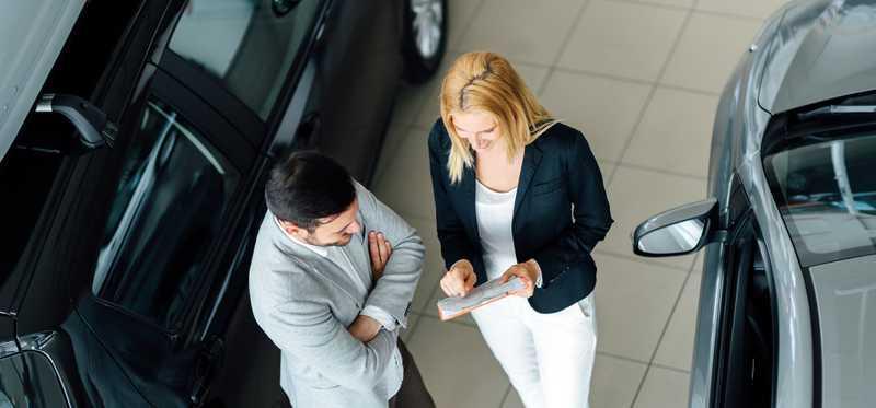 A man and a woman negotiate at a car dealer