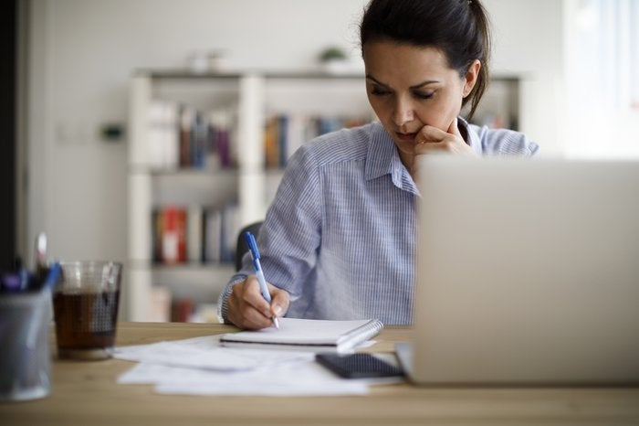 Woman sitting at table with computer and paying bills