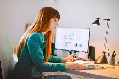 Red haired woman sitting at desk with computer while reviewing financial charts