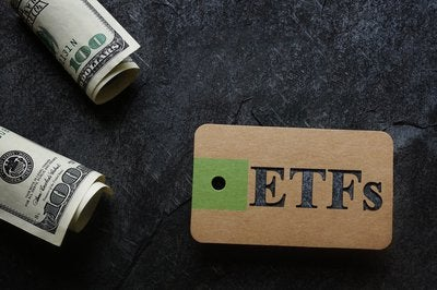 A tag with the acronym ETFs written on it with $100 bills nearby.