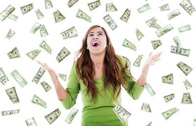 Young woman in green dress looking toward the sky as money falls down around her