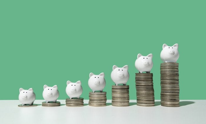 Little white piggy banks standing on top of 7 stacks of coins in ascending order on white surface, green background.