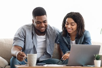 Couple smiling while looking at papers and laptop
