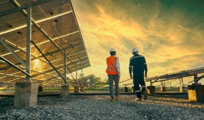Two people walking near solar energy panels with a sunset in the background.