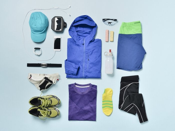 Jogging clothes and accessories organized on blue back.Items include: Smart Watch,smartphone