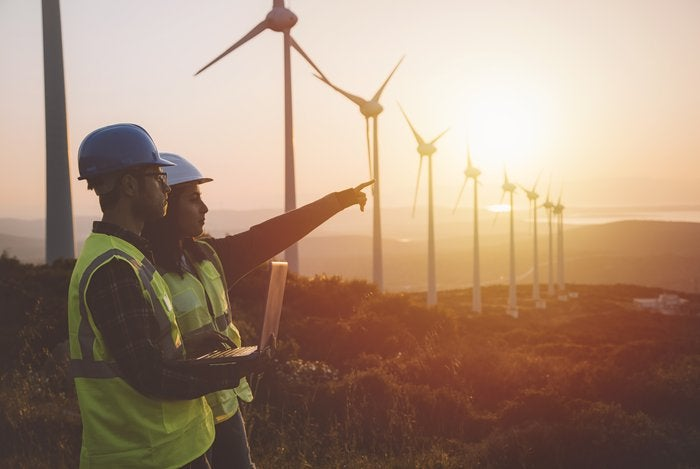 Utilities workers with wind turbines