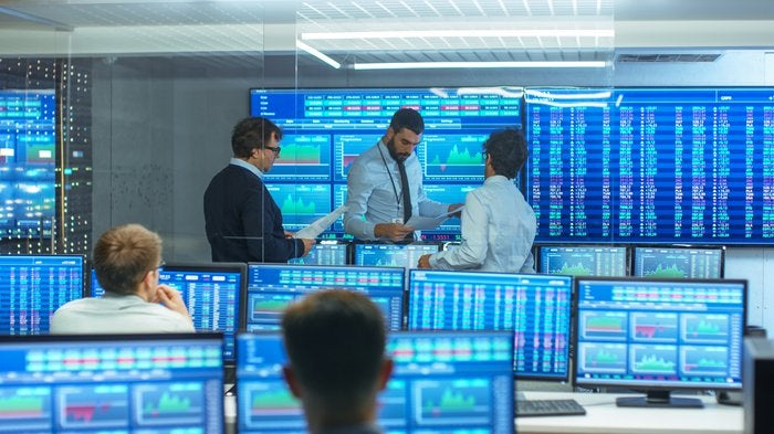 Stock traders discussing charts and surrounded by displays of market data.