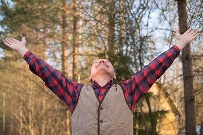 A man looking up in happiness with arms outstretched.