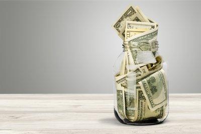 A glass jar stuffed full of cash