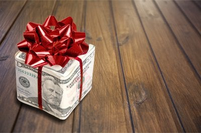 A gift box wrapped in money and a bow.