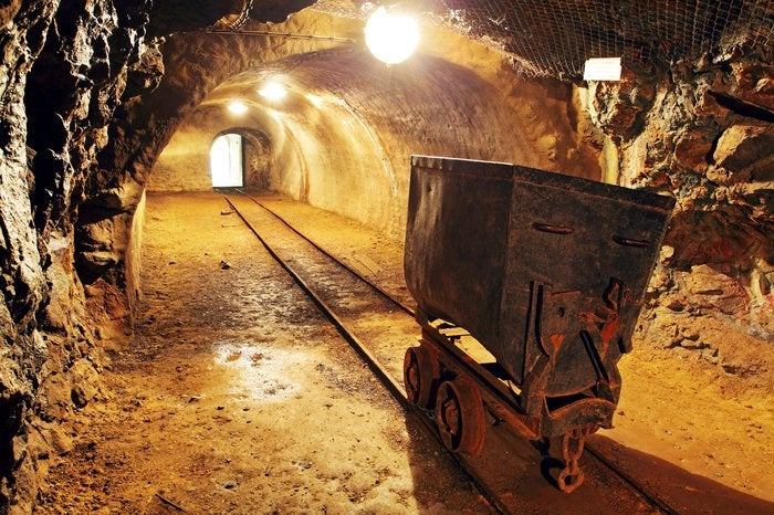 Gold mine cart on its railroad track in a mine tunnel with a golden background