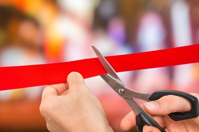 Hand with scissors cutting a red ribbon