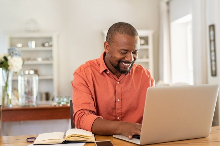 Happy mature man typing on laptop