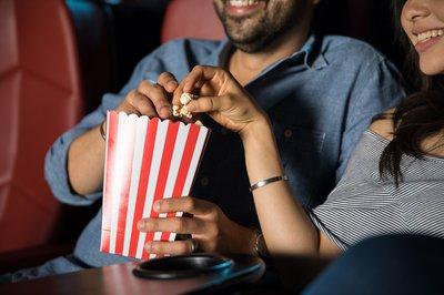 Two moviegoers share popcorn.